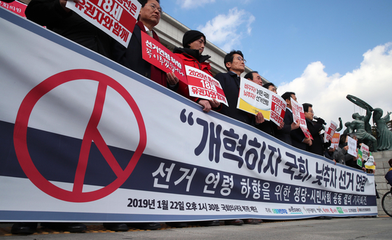 지난 1월 22일 오후 서울 여의도 국회의사당 본청 앞에서 열린 선거연령 하향을 위한 정당-시민사회 공동 결의 기자회견에서 참가자들이 손팻말을 들고 있다. [연합뉴스]