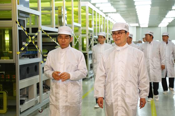 파주에서 열린 탑엔지니어링 기자간담회에서 류도현 탑엔지니어링 대표(왼쪽)와 박원주 특허청장이 LCD 디스펜서 파주 생산공장을 둘러보고 있다. [사진 특허청]