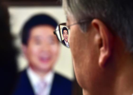 2015년 4월23일 국회 새정치민주연합 대표실에서 '성완종 리스트' 파문과 관련해 긴급 기자회견을 갖던 문재인 대표 안경에 고 노무현 전 대통령의 얼굴이 비치고 있다. <이병화기자/ 아시아투데이/ 한국사진기자협회>