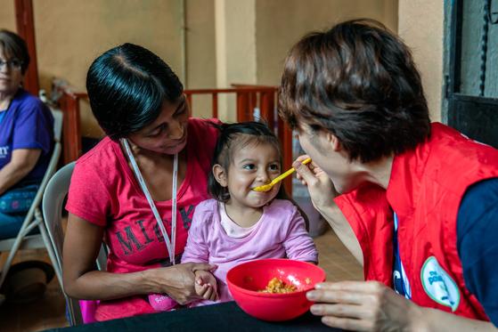 한국에서 과테말라 컴패션 어린이센터를 방문한 후원자가 이유식에 영양제를 섞어 후원 어린이에게 사랑을 담아 먹여주고 있다. 딸이 건강하게 성장할 수 있어서 감사하다는 엄마의 미소가 오랫동안 기억에 남는다. [사진 한국컴패션]