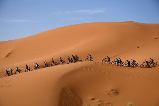'2019 가민 티탄 사막 산악자전거' 대회가 28일(현지시간) 모로코 메르주가 사막에서 개막했다. 출전 선수들이 사막의 모래 언덕을 오르고 있다. [AFP=연합뉴스]