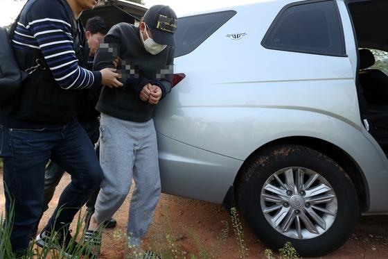 의붓딸(13)을 살해하고 시신을 저수지에 버린 혐의(살인 및 사체유기)로 구속된 김모(31)씨가 지난 1일 전남 무안군 한 농로에서 범행을 재연하고 있다. [연합뉴스]