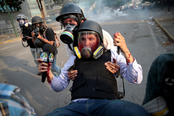 1일(현지시간) 베네수엘라 수도 카라카스에서 열린 반정부 시위를 취재 중이던 기자가 부상을 당해 동료에 의해 현장에서 후송되고 있다. [로이터=연합뉴스]