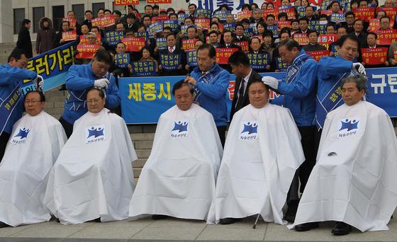 자유선진당 의원들이 2010년 1월 11일 오전 국회 본관에서 열린 세종시 원안 사수 결의대회에 참석해 삭발식을 하고 있다. [중앙포토]