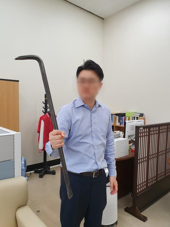 자유한국당 나경원 원내대표실 직원이 빠루를 들어 보이고 있다. 지난 26일 새벽 더불어민주당 당직자들과의 치열한 몸싸움 도중 획득한 것이라고 했다. [조강수 기자]