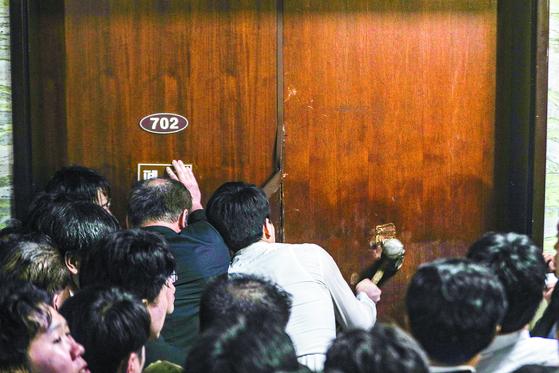 지난 26일 새벽 국회 본관 7층에서 더불어민주당 당직자와 방호과 직원 등이 패스트트랙 지정 안건 법안 제출을 위해 빠루와 쇠망치를 동원해 의안과 진입을 시도하고 있다. [뉴스1]