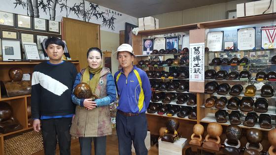 공방 한쪽에 마련된 목탁 전시장에 김덕주 명인 부부와 목탁 일을 배우는 아들 김영길 씨(왼쪽)가 함께 자리했다. 부인은 목탁을 마케팅하는 역할을 맡고 있다. [사진 송의호]