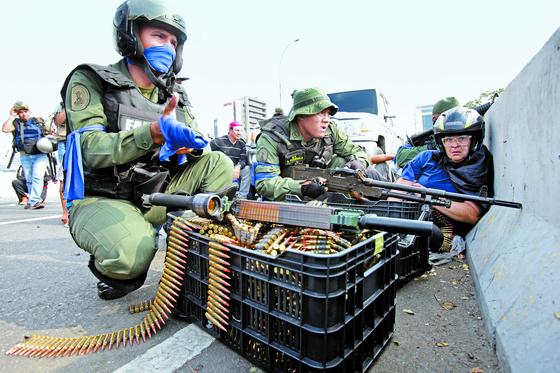 시위대에 합류한 베네수엘라 군인들이 지난달 30일(현지시간) 카라카스 에서 정부군과 대치 하고 있다. 시위대에 합류한 군인들은 파란색 리본을 팔에 감았다.