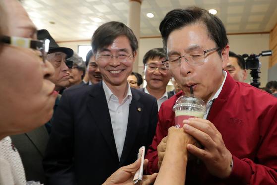 장외 투쟁에 본격 돌입한 황교안 자유한국당 대표가 3일 오후 전북 전주시 전주역에서 '문재인 STOP! 전주 시민이 심판합니다' 규탄 대회를 마친 뒤 대합실에서 인사를 하다 지지자가 건넨 음료를 받아 마시고 있다[뉴스1]