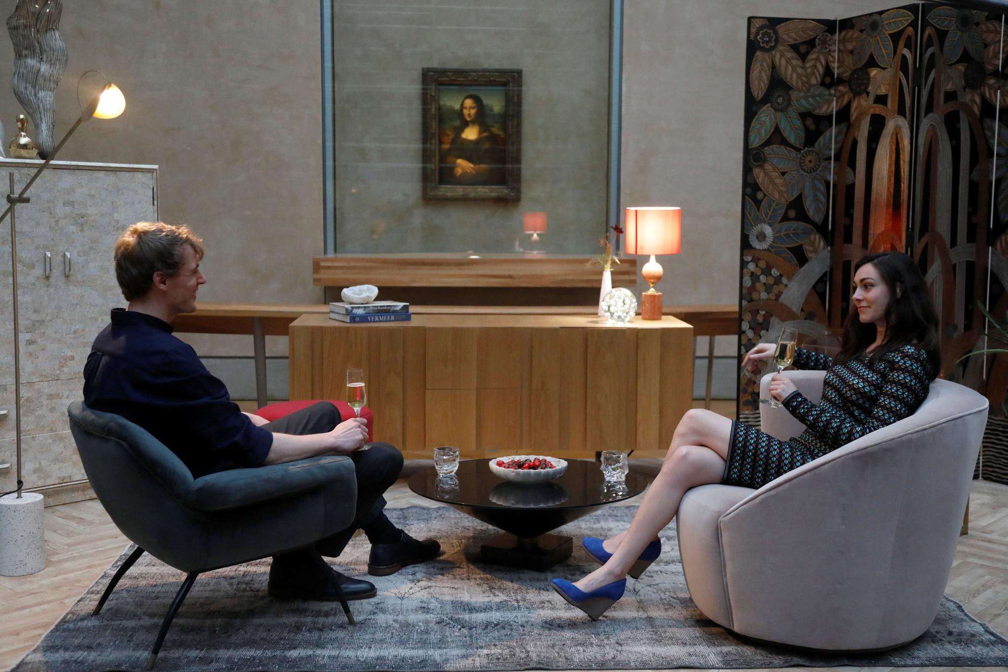 에어비앤비 이벤트에 당첨된 다니엘라와 아담이 지난달 30일(현지시간) 프랑스 파리 루브르 박물관 '모나리자' 앞에서 식전주를 마시고 있다. [로이터=연합뉴스]