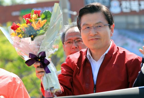 장외 투쟁에 본격 돌입한 황교안 자유한국당 대표가 3일 오후 전북 전주시 전주역 광장에서 '문재인 STOP! 전주 시민이 심판합니다' 규탄 대회 전 꽃다발을 받고 미소를 짓고 있다.[뉴스1]