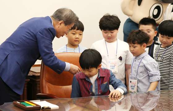 문재인 대통령이 5일 청와대 본관 집무실에서 제97회 어린이날 청와대 초청행사에 참석한 어린이들을 대통령 집무실 의자에 앉히고 있다. [뉴시스]
