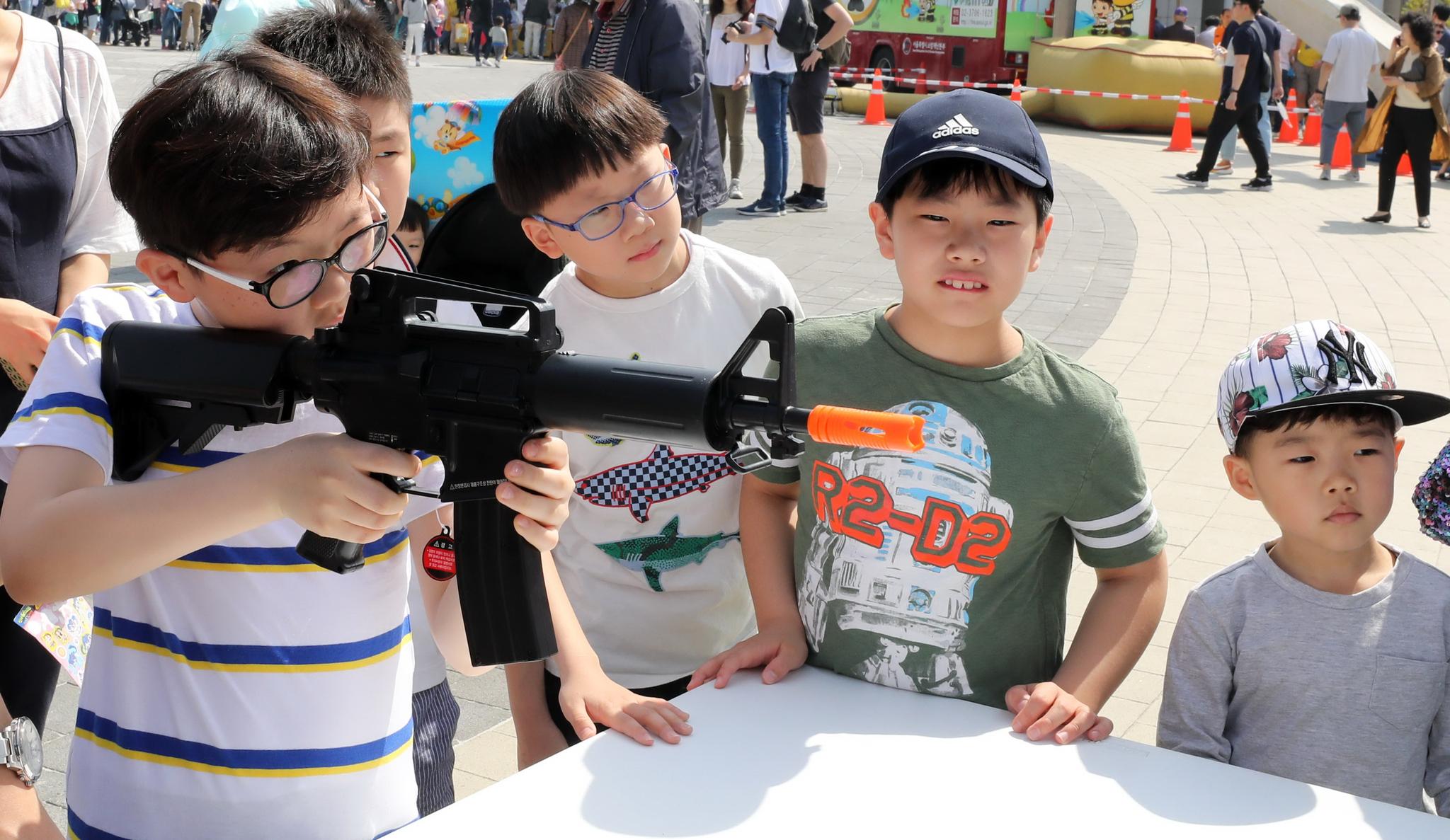 서울 용산 전쟁기념관에서 열린 '어린이날 문화축제'에 참가한 어린이들이 전동건 사격체험을 하고 있다. [뉴시스]