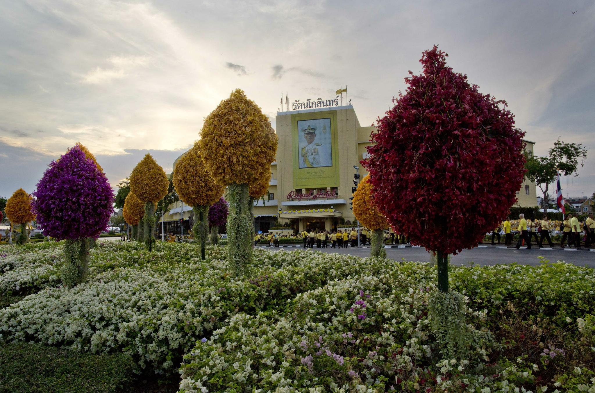 노란 옷을 입은 태국 국민들이 화려한 꽃으로 장식된 길을 따라 국왕의 대관식 행렬을 보기 위해 이동하고 있다. [AP=연합뉴스]