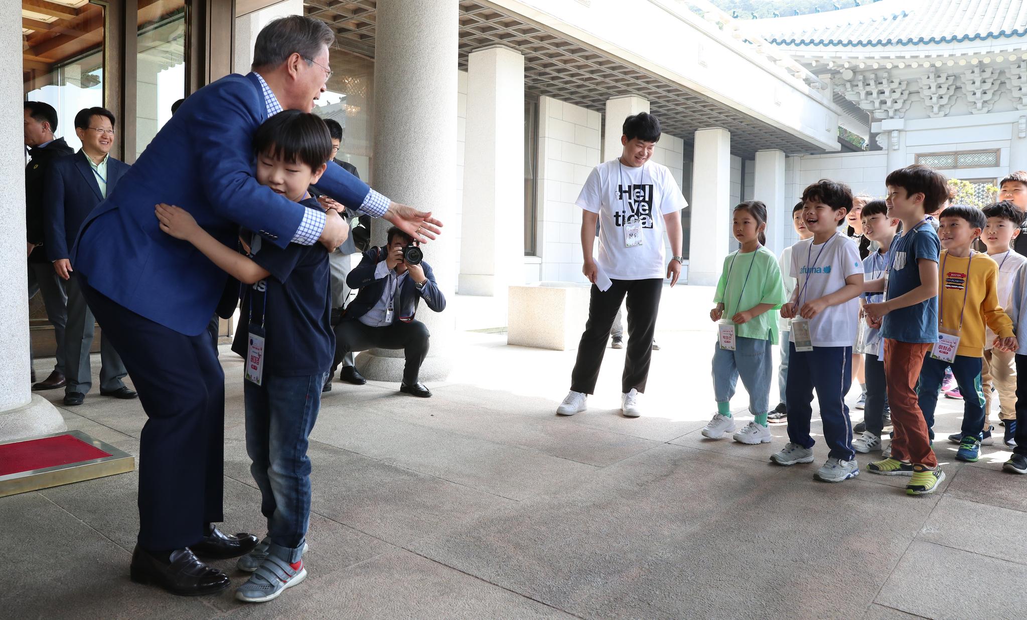 문재인 대통령이 5일 청와대 본관 앞에서 한 어린이를 안아주며 뒤따라 오던 아이들도 맞이하고 있다. 청와대사진기자단