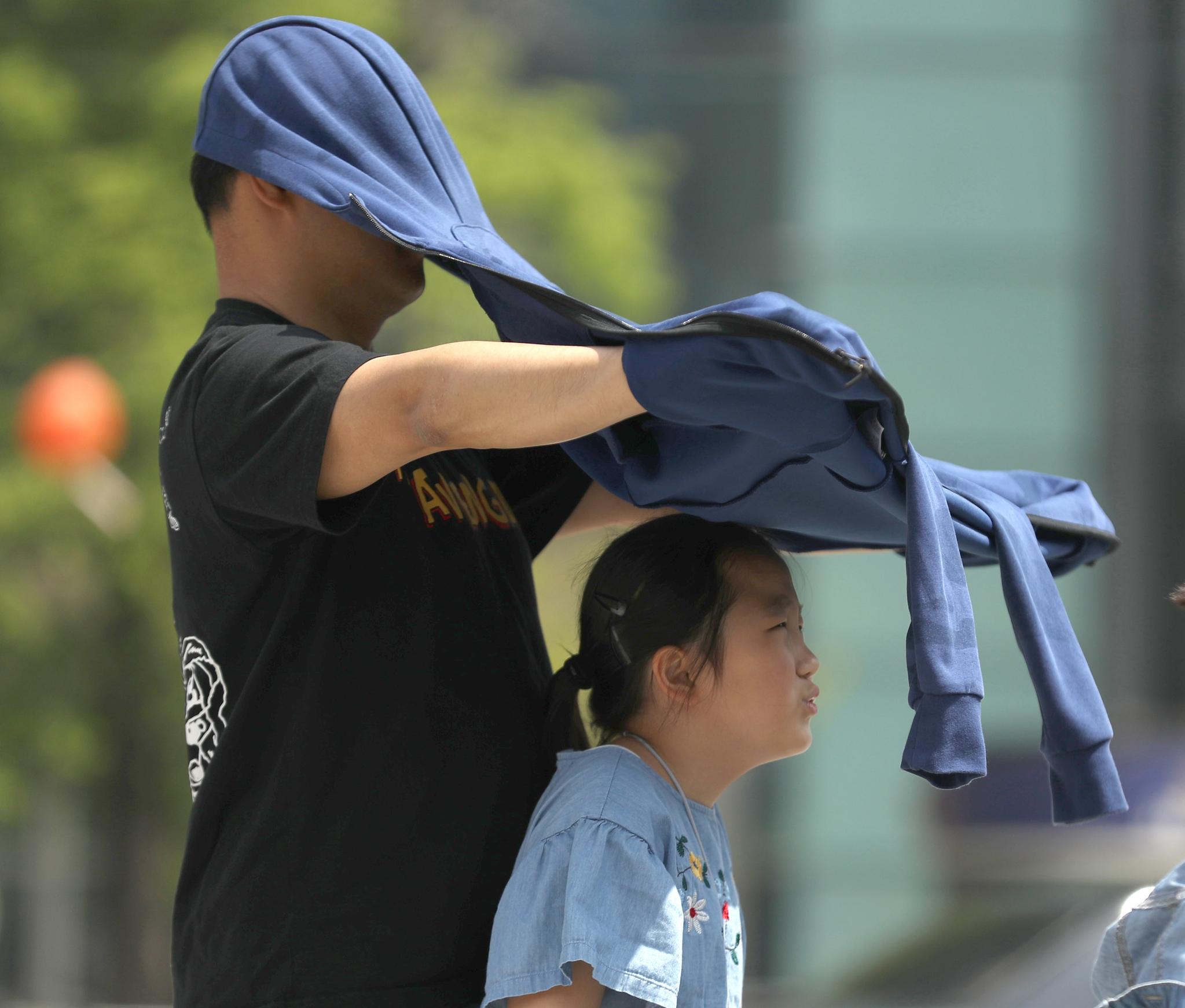 서울 보신각에서 열린 '어린이날 희망타종행사'에 참가한 딸에게 아빠가 그늘을 만들어주고 있다. [연합뉴스]