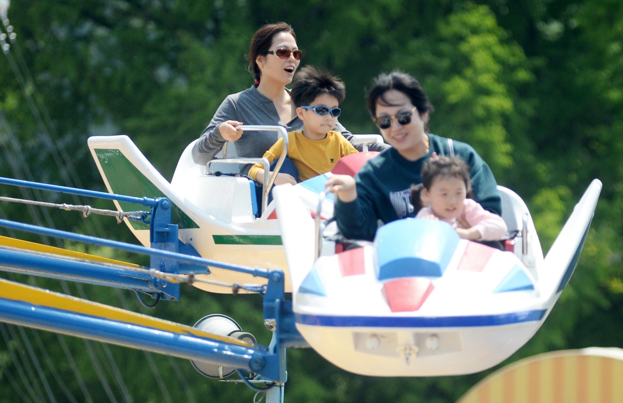 5일 전북 전주동물원 놀이동산을 찾은 부모와 어린이들이 놀이기구를 타며 즐거워하고 있다. [뉴시스]