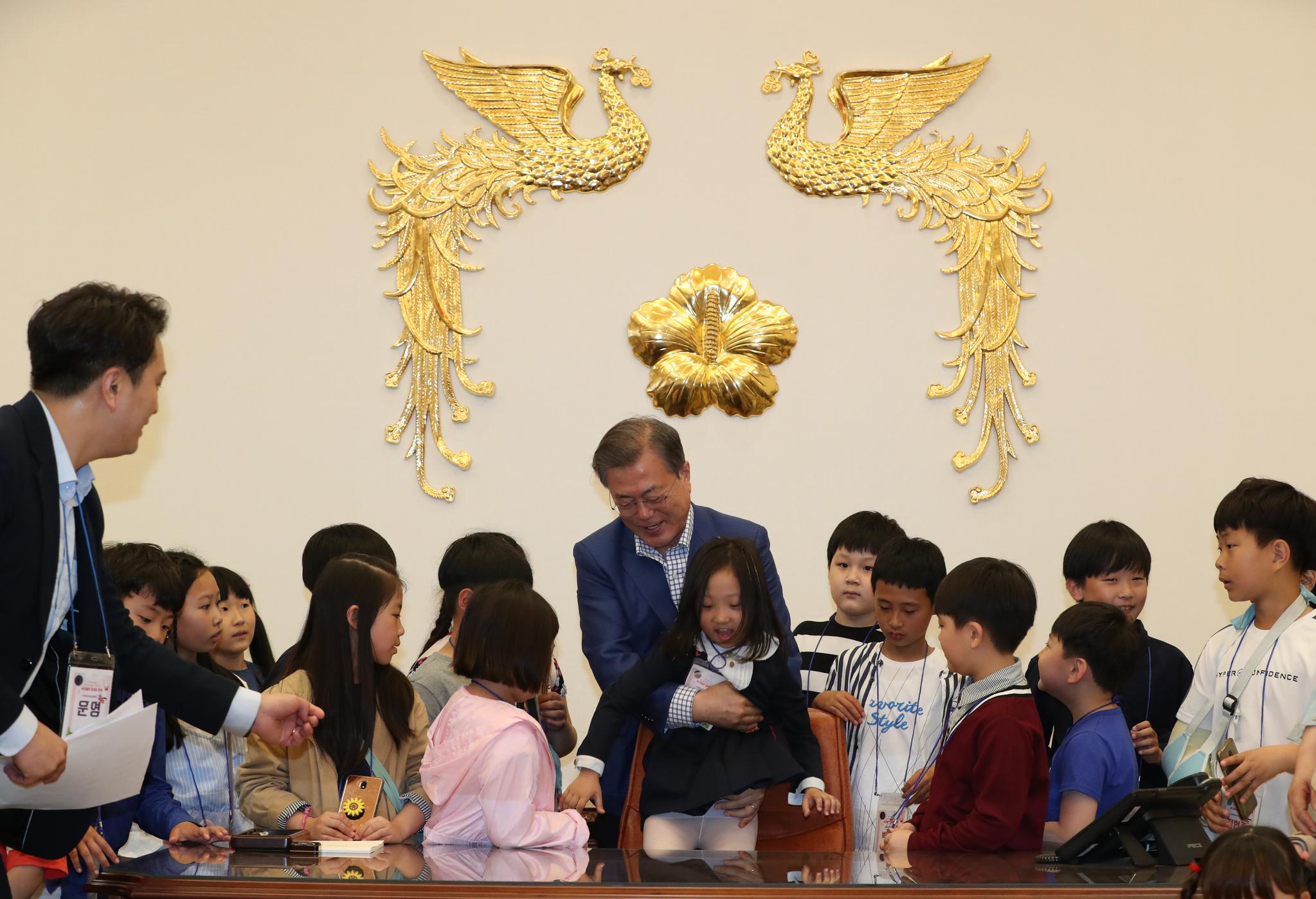문재인 대통령이 5일 본관 집무실에서 한 어린이를 '대통령 의자'에 앉히고 있다. 청와대사진기자단