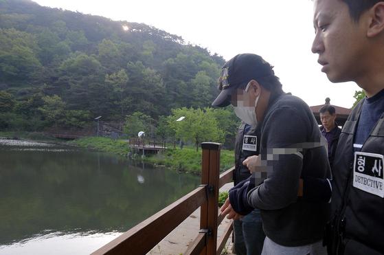 중학생 의붓딸(13)을 살해하고 시신을 강에 유기한 혐의로 구속된 A씨(31)가 1일 광주 동구 한 저수지에서 범행 당시 상황을 재연하고 있다. [뉴스1]