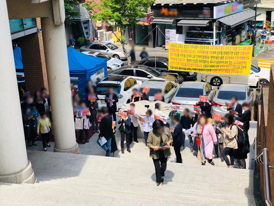 5일 오전 11시쯤 서울 강남구 대치동 S교회 원로목사 측 교인들이 팻말을 들고 2층 출입구를 바라보고 있다. 남궁민 기자