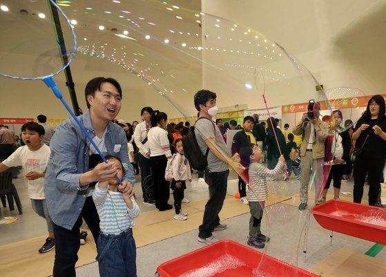 1일 서울 동대문구 동대문디자인플라자(DDP)에서 열린 '서울학생 더불어 큰 숲 놀이 대축제'에서 어린이들이 아빠와 함께 비누방울 놀이를 하고 있다. [뉴스1]
