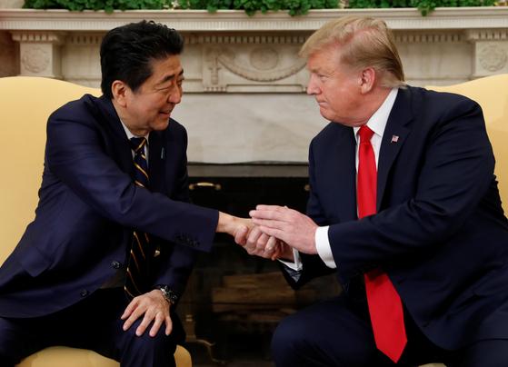 한국시간 27일 미국 백악관에서 악수하는 도널드 트럼프 미국 대통령(오른쪽)과 아베 신조 일본 총리. [로이터=연합뉴스]
