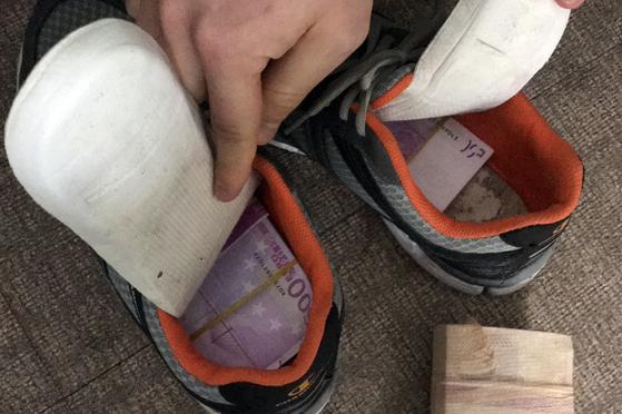 경남지방경찰청은 7일 오전 신발과 속옷에 외화를 숨겨 1천억원대 외화를 밀반출한 일당을 검거했다고 밝혔다. 사진은 운반책이 신발에 외화를 숨긴 모습. [경남지방경찰청 제공=연합뉴스]