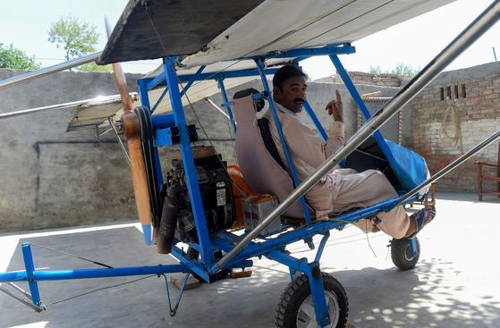 무하마드 페이야즈 씨가 지난 8일(현지시간) 자신이 손수 만든 경비행기에 올라 포즈를 취하고 있다. [AFP=연합뉴스]