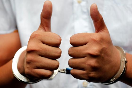 와 론 기자가 지난해 9월 법원을 나서며 수갑찬 손으로 엄지를 들어보이고 있다. [로이터=연합뉴스]