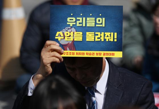 지난 3월 23일 서울 청계광장에서 열린 강사 구조조정 저지와 학습권 보장 결의대회에서 참가자가 수업권을 요구하는 피켓을 들고 있다. [연합뉴스]