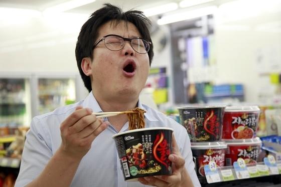 편의점에서 한 소비자가 매운 라면을 먹고 있다. 경기 불황이 이어지면서 강렬한 맛으로 스트레스를 해소하려는 소비자가 늘고 있다. [중앙포토]