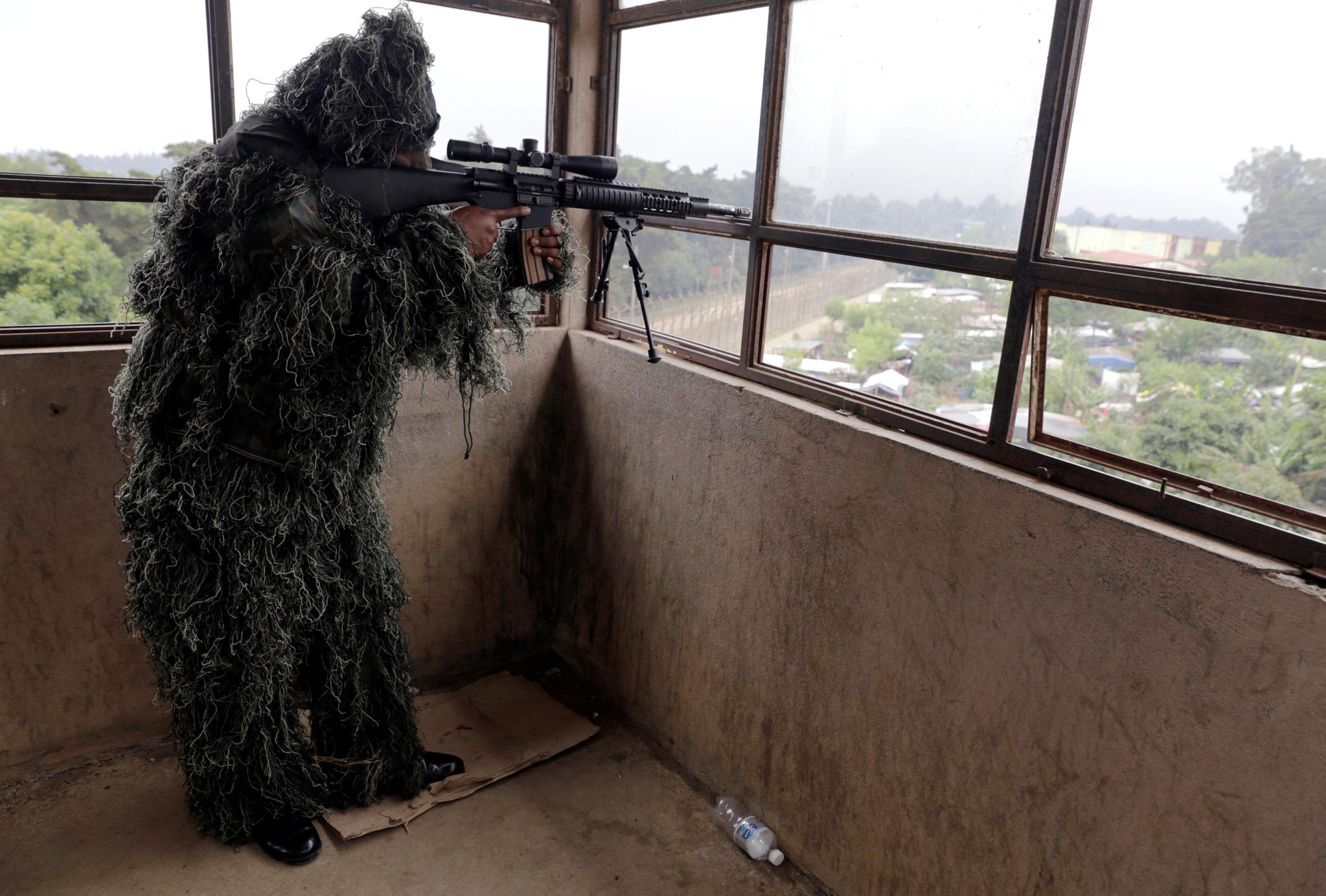 위장을 한 군인이 파본 교도소가 내려다 보이는 곳에서 경계 근무를 서고 있다. [로이터=연합뉴스]