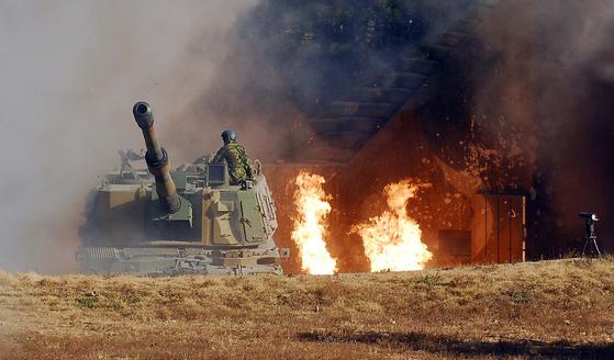 2010년 연평도 포격 도발 당시 해병대 K-9 진지 포상에 북한군이 쏜 포탄이 떨어져 화염에 휩싸인 가운데, 해병대원이 대응 사격준비를 하고 있다.