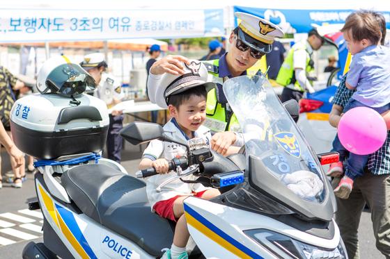 한 어린이가 경찰의 지도를 받으며 경찰 오토바이에 올라 타 있다.[사진 서울시]