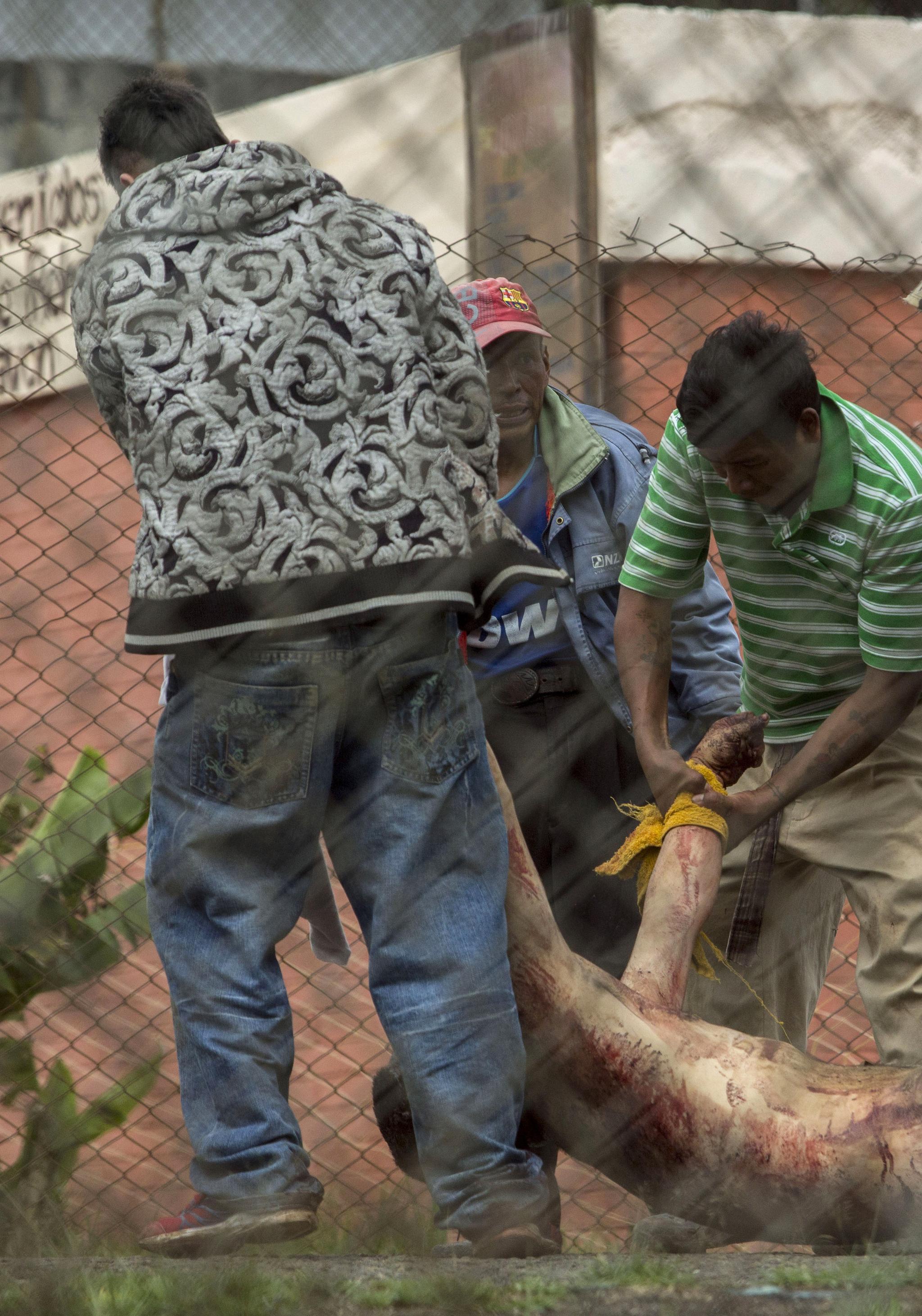 파본 교도소 재소자들이 총격을 받고 사망한 수감자의 시신을 수습하고 있다. [AP=연합뉴스]