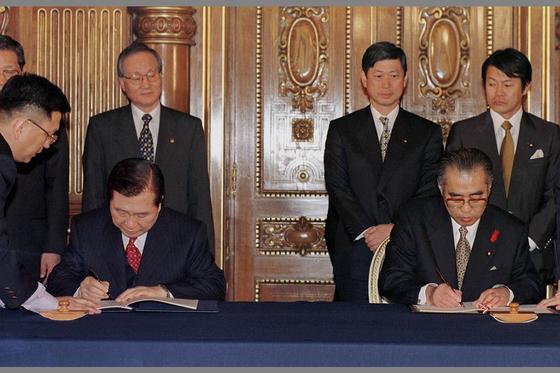 일본을 국빈방문중인 김대중 대통령과 오부치 게이조(小淵惠三) 일본 총리가 8일 도쿄 영빈관에서 양국 외무장관이 지켜보는 가운데 '21세기 새 시대를 위한 공동선언'협정서에 서명하고 있다. [중앙포토]