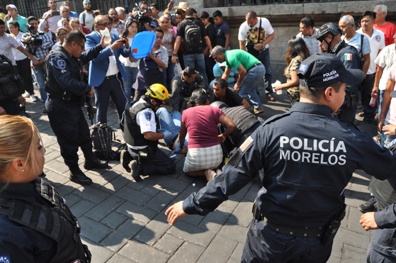 경찰 등 구조대원이 8일 (현지시간) 멕시코 모렐로스 주 쿠에르나바카에서 발생한 총격으로 부상당한 남성을 응급처치하고 있다. [AFP=연합뉴스]