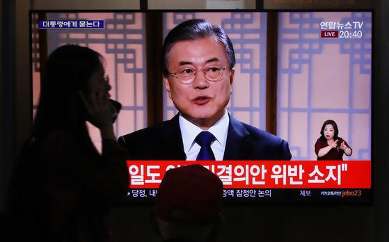 9일 오후 서울역에서 시민들이 문재인 대통령 취임 2주년 특집 대담' 대통령에게 묻는다'를 TV로 시청하고 있다. [연합뉴스]