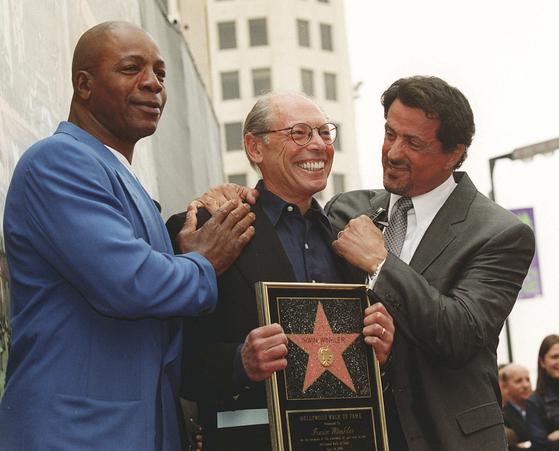실베스터 스탤론(오른쪽)이 지난달 할리우드 명예의 거리에서 영화 '록키'(1976)의 제작자 어윈 윙클러(가운데)를 축하하는 모습. 왼쪽은 '록키'에서 '아폴로' 역할을 맡았던 배우 칼 웨더스. 스탤론이 주연과 각본을 맡은 '록키'로 아카데미 작품상을 받았던 윙클러는 최근 영화 인생 50년을 돌아보는 자서전을 펴냈다. [AP=연합뉴스]