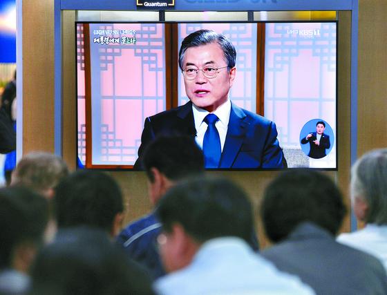 9일 오전 서울역 대합실에서 시민들이 문재인 대통령의 취임 2주년 특집 대담 방송을 보고 있다. [뉴스1]