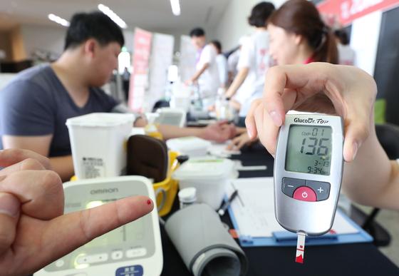 지난해 9월 정부세종청사에서 심뇌혈관질환 예방관리 캠페인이 열려 직원들이 혈압·혈당·측정을 하고 있다. [연합뉴스]