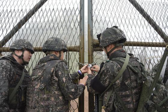 지난해 11월 비무장지대 감시초소 입구에 자물쇠를 채우는 국군 장병들. DMZ 내 출입은 철저히 군부대의 협조로 이뤄지기 때문에, 반달가슴곰의 생태조사 장비도 군 부대에 부탁해 설치한다. 보안 때문에 생태 전문가가 직접 들어가지 못하고, 곰이 다닐만한 최적의 위치가 아닌 사람이 다니는 길 위주로 장비가 설치된다. [뉴스1]
