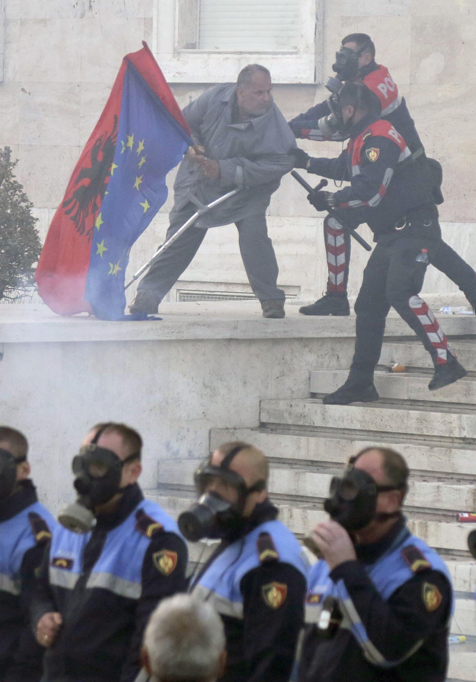 알바니아 국기와 유럽 연합기를 든 한 시위대가 경찰 저지선을 돌파하자, 경찰들이 이를 제지하고 있다. [EPA=연합뉴스]