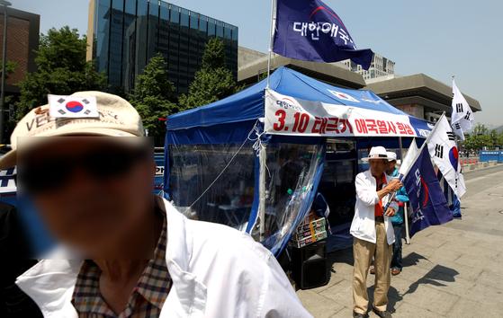 대한애국당 당원들이 지난 11일 서울 광화문광장에 설치한 천막 앞에서 구호를 외치고 있다. [뉴스1]