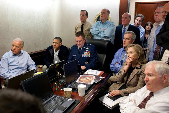 2011년 5월 1일(현지시간) 워싱턴 백악관의 상황실에서 버락 오바마 당시 대통령과 안보팀이 오사마 빈 라덴 제거 작전인 '제로니모 E-KIA'의 진행 상황을 실시간 영상으로 지켜보고 있다. 골프복 차림의 오바마 대통령은 작전을 설명하는 마셜 웹 합동특수전사령부 부사령관에게 대통령 의자를 양보하고 구석에 자리를 잡았다. 힐러리 클린턴 국무장관은 빈 라덴이 총에 맞아 쓰러지는 장면을 보곤 놀란 표정으로 입을 가리고 있다. 왼쪽부터 조 바이든 부통령, 오바마 대통령, 웹 부사령관, 데니스 맥도너 국가안보 부보좌관, 클린턴 국무장관, 로버트 게이츠 국방장관. [미 백악관 웹사이트]