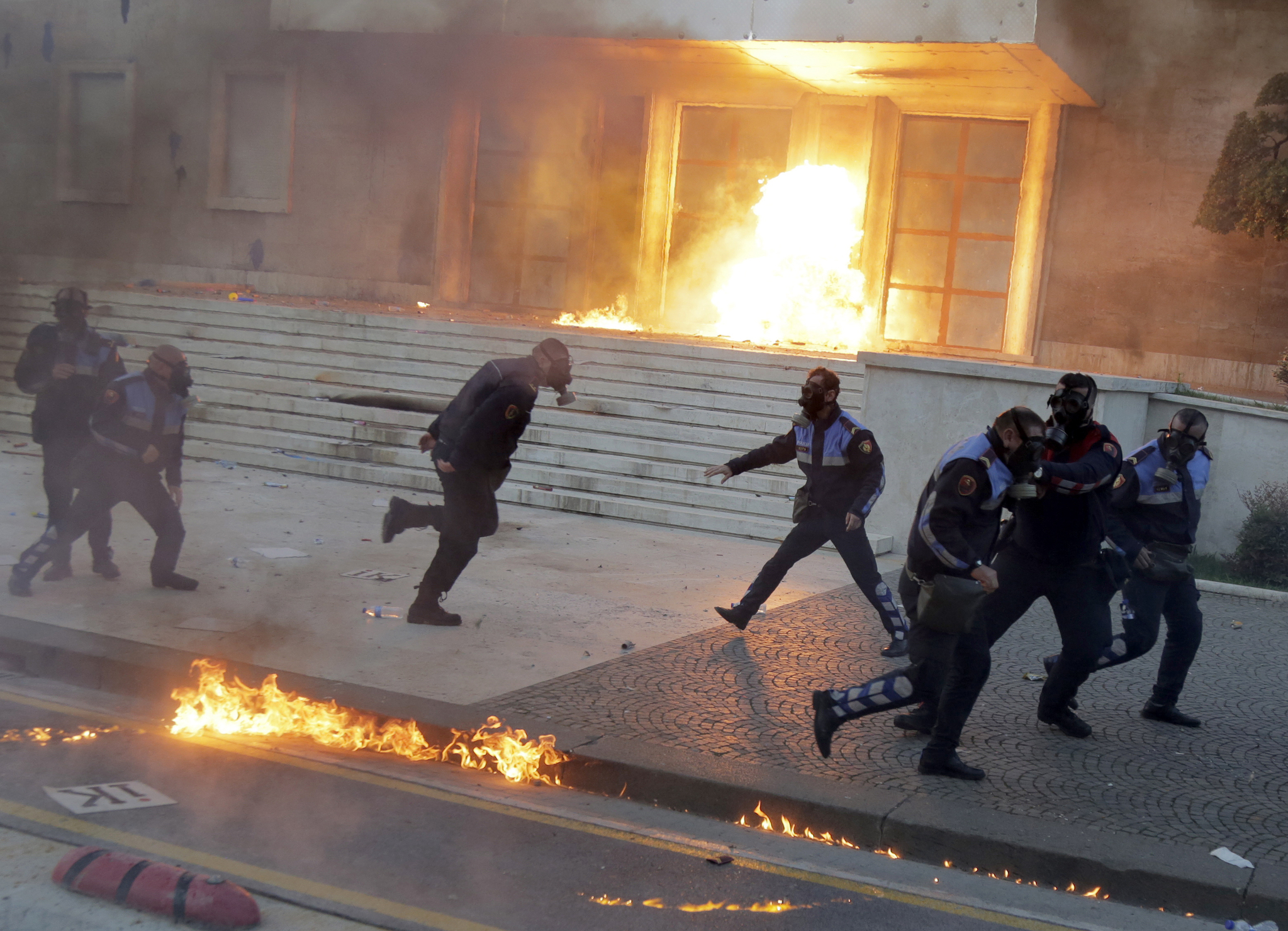 11일(현지시간) 알바니아 수도 티라나의 정부 청사 건물에 반정부 시위대들이 터트린 휘발유 폭탄으로 불길이 치솟고 있다. 정부 청사 건물이 불길과 최루탄 연기로 자욱한 가운데 방독면을 쓴 경찰들이 폭발을 피해 다급히 움직이고 있다. [EPA=연합뉴스]