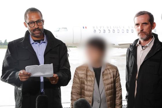 아프리카 부르키나파소에서 납치됐다가 프랑스 특수부대에 구출된 한국인 여성(가운데)과 프랑스인 남성 2명이 11일(현지시간) 프랑스 파리 근교 빌라쿠블레 군 비행장에 도착, 기다리고 있던 취재진에게 말하고 있다. [연합뉴스]
