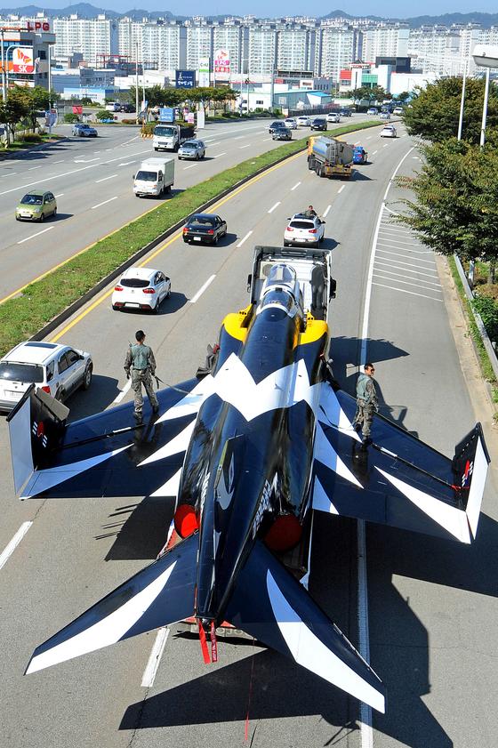 지난 2013년 10월 F-4E 팬텀 전투기가 공군 제17전투비행단에서 퇴역해 충북 청원군 공군사관학교로 이송되고 있다. 공군 에어쇼 항공기인 블랙이글과 같은 도색으로 꾸며진 이 전투기는 공군사관학교에 전시됐다. 일부가 여전히 현역으로 활동 중이지만 어느덧 시급히 교체되어야 할 노후 기종이 되었다. [사진 =뉴스1]