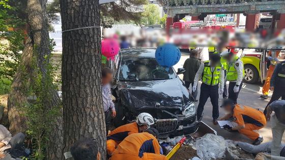 부처님오신날인 12일 소방대원과 경찰이 경남 양산시 통도사 진입로에서 발생한 교통사고 부상자들을 구조하고 있다. 이 사고로 1명이 숨지고 12명이 중경상을 입었다. [사진 경남지방경찰청]