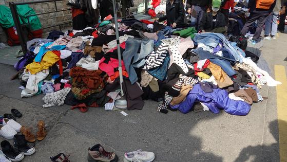 산더미처럼 쌓아 놓은 구제 옷가지에서 옷을 고르고 입어보는 사람들의 모습을 쉽게 볼 수 있다.